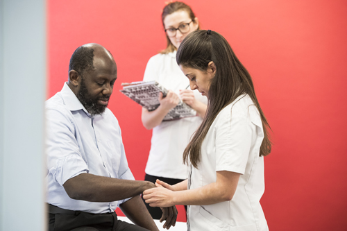 An osteopathy student being assessed whilst treating a patient