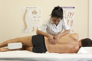 Female osteopath treating male back