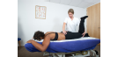 Female osteopath treating lower back and legs