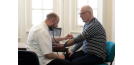 Osteopath with middle-aged man consultation 2
