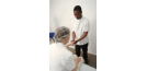 Male osteopath treating female patient's hand