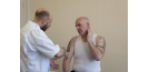 Male osteopath and middle aged man - exercise