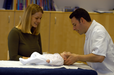 Male osteopath with child and mother