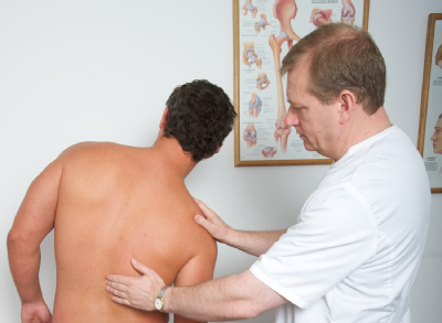Male osteopath with male patient - back