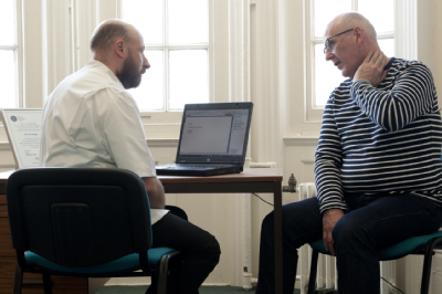 Osteopath and middle-aged man consultation