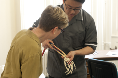 Osteopath with woman - skeleton arm