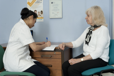 Female osteopath consultation with elderly woman