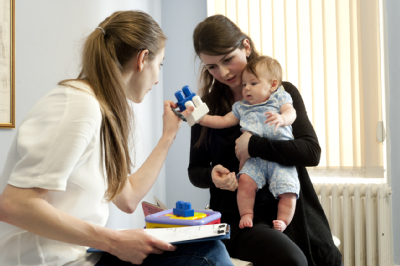 Female osteopath with mother and baby