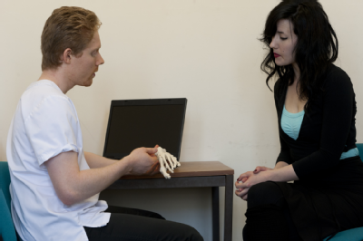 Male osteopath consultation with young woman