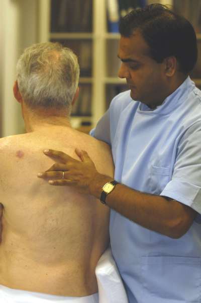 Male osteopath and middle aged man - back