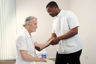 Osteopath and elderly woman - arms