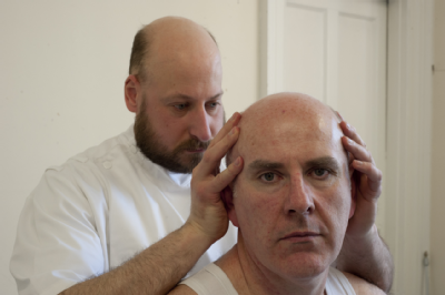 Osteopath with middle-aged man - head